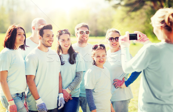 group of volunteers taking picture by smartphone Stock photo © dolgachov