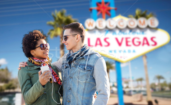 couple with smartphone and earphones at las vegas Stock photo © dolgachov