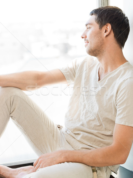 man in casual clothes sitting on the windowsill Stock photo © dolgachov