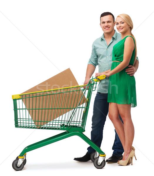 smiling couple with shopping cart and big box Stock photo © dolgachov
