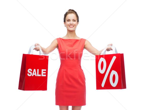 Fiatal nő vörös ruha bevásárlótáskák vásárlás vásár ajándékok Stock fotó © dolgachov