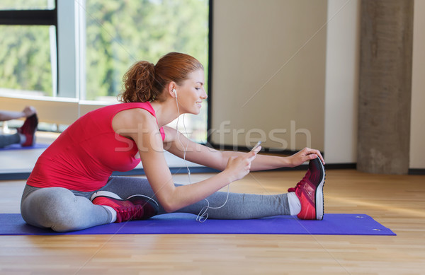 5550913_stock-photo-smiling-woman-stretching-on-mat-in-the-gym.jpg
