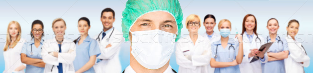 surgeon in medical cap and mask over team Stock photo © dolgachov