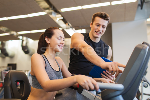 happy woman with trainer on exercise bike in gym Stock photo © dolgachov