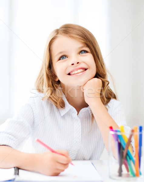 Stock photo: smiling little student girl drawing at school
