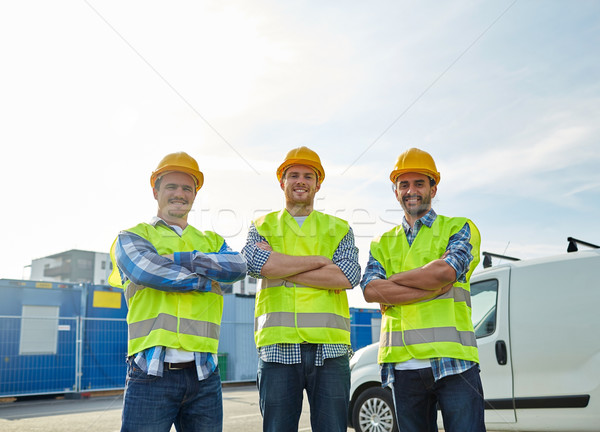 happy male builders in high visible vests outdoors Stock photo © dolgachov