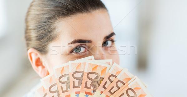 woman hiding her face behind euro money fan Stock photo © dolgachov