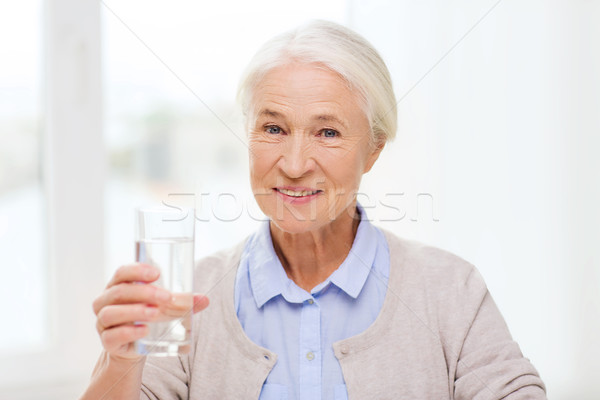 happy senior woman with glass of water at home Stock photo © dolgachov
