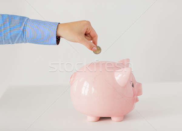 close up of hand putting coin into piggy bank Stock photo © dolgachov