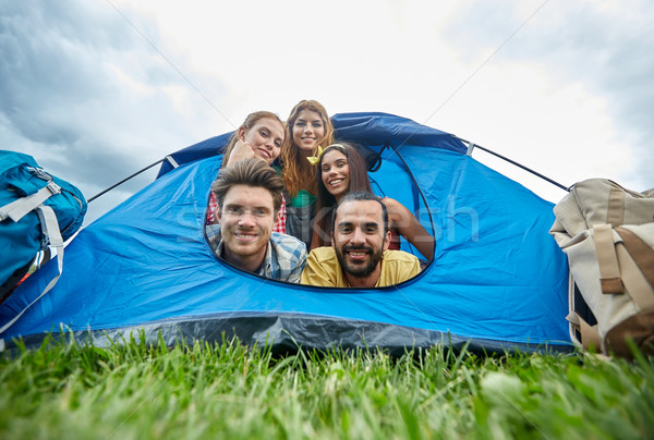 happy friends with backpacks in tent at camping Stock photo © dolgachov