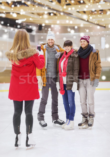 Stock photo: happy friends taking photo on skating rink