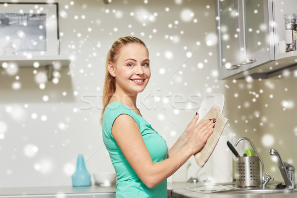 happy woman wiping dishes at home kitchen Stock photo © dolgachov
