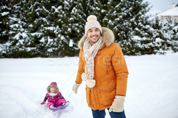 happy man carrying little kid on sled in winter Stock photo © dolgachov