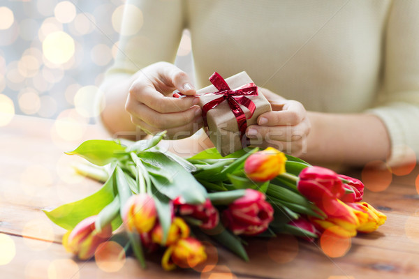Stock photo: close up of woman with gift box and tulip flowers
