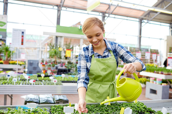 happy woman with watering can in greenhouse Stock photo © dolgachov