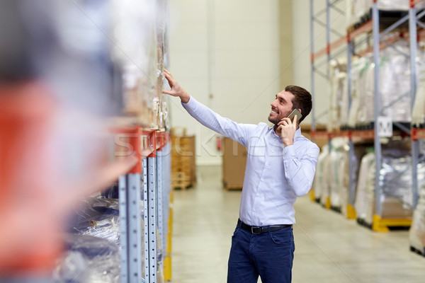 happy man calling on smartphone at warehouse Stock photo © dolgachov
