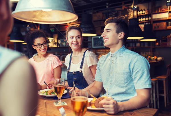 Feliz amigos alimentação potável bar pub Foto stock © dolgachov