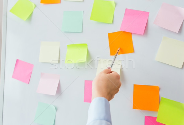close up of hand pointing to sticker on flip chart Stock photo © dolgachov