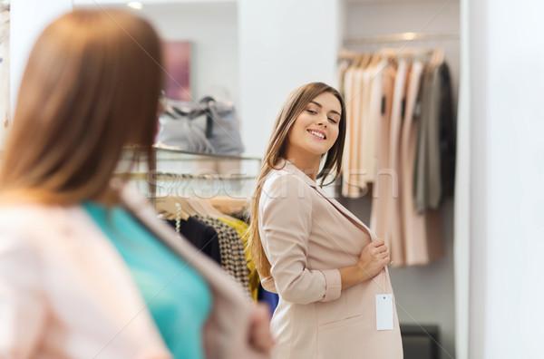 happy woman posing at mirror in clothing store Stock photo © dolgachov