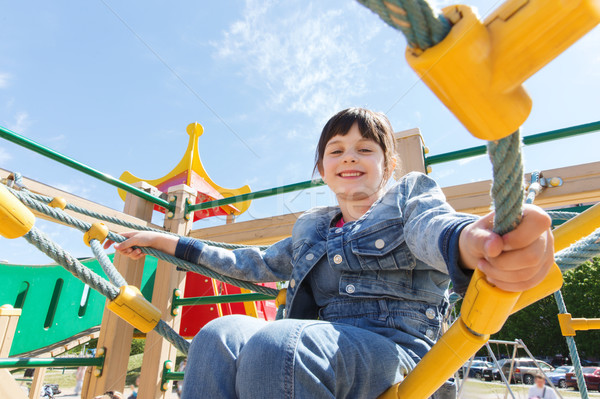 happy little girl climbing on children playground Stock photo © dolgachov