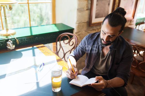 Człowiek piwa piśmie notebooka bar publikacji Zdjęcia stock © dolgachov