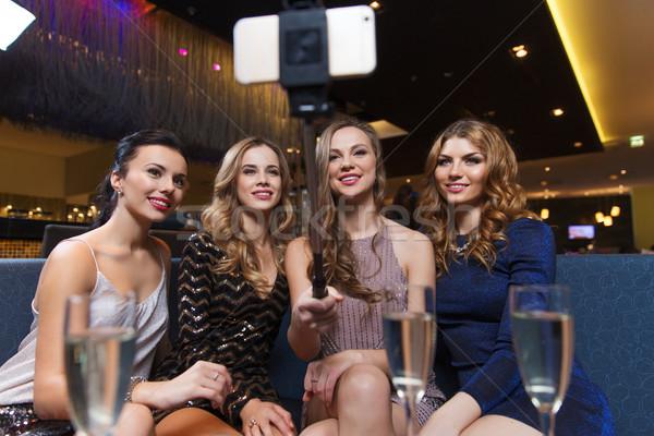 Donne smartphone night club celebrazione amici Foto d'archivio © dolgachov