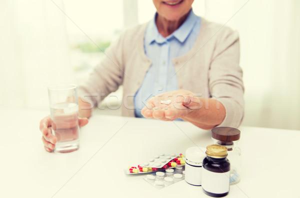 Felice senior donna acqua pillole home Foto d'archivio © dolgachov