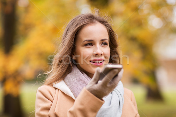 woman recording voice on smartphone in autumn park Stock photo © dolgachov