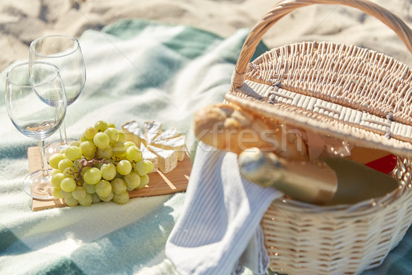 picnic basket with wine glasses and food on beach Stock photo © dolgachov
