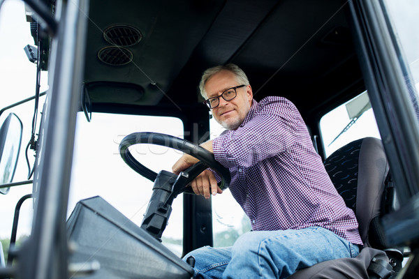 senior man in tractor at farm Stock photo © dolgachov