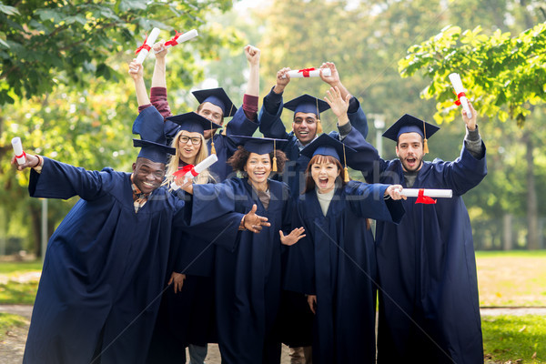 happy students in mortar boards with diplomas Stock photo © dolgachov