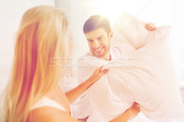 Stock photo: happy couple having pillow fight in bed at home