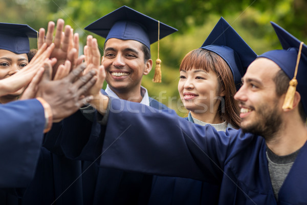 happy students in mortar boards making high five Stock photo © dolgachov