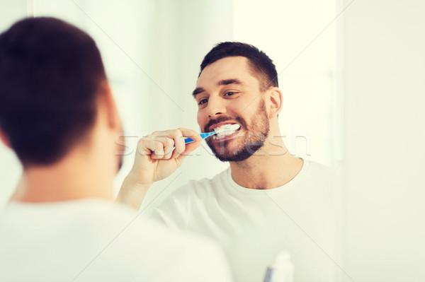 man with toothbrush cleaning teeth at bathroom Stock photo © dolgachov