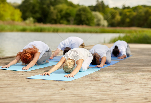 group of people making yoga exercises outdoors Stock photo © dolgachov
