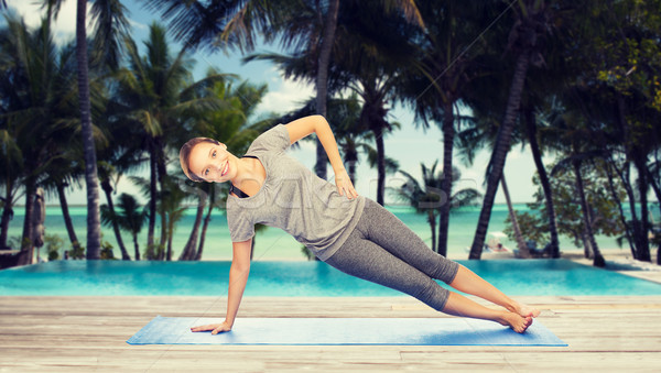 woman making yoga in side plank pose on mat Stock photo © dolgachov