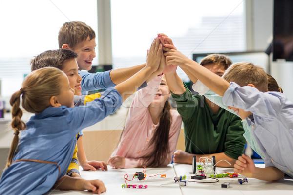 happy children making high five at robotics school Stock photo © dolgachov