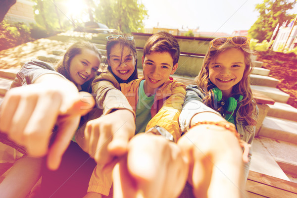 Stock photo: teenage friends or students pointing finger at you