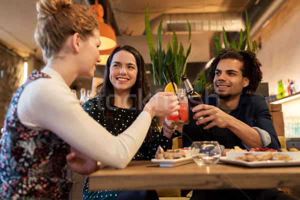 happy friends clinking drinks at bar or cafe Stock photo © dolgachov