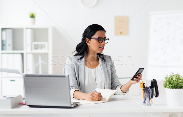 Stock photo: businesswoman with smartphone and laptop at office