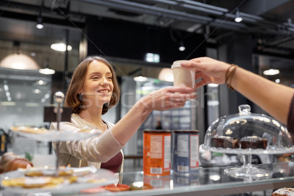 happy woman taking coffee cup from seller at cafe Stock photo © dolgachov