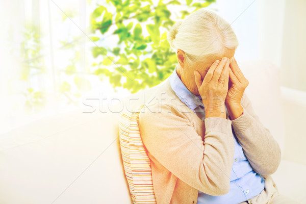 senior woman suffering from headache or grief Stock photo © dolgachov