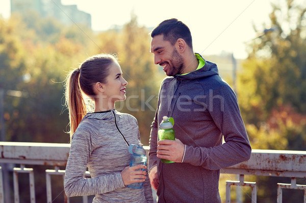 smiling couple with bottles of water outdoors Stock photo © dolgachov