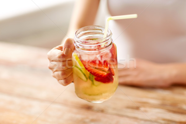 close up of woman holding glass with fruit water Stock photo © dolgachov