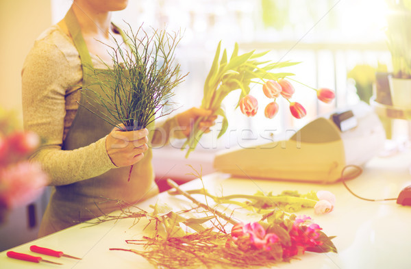 close up of florist making bunch at flower shop Stock photo © dolgachov