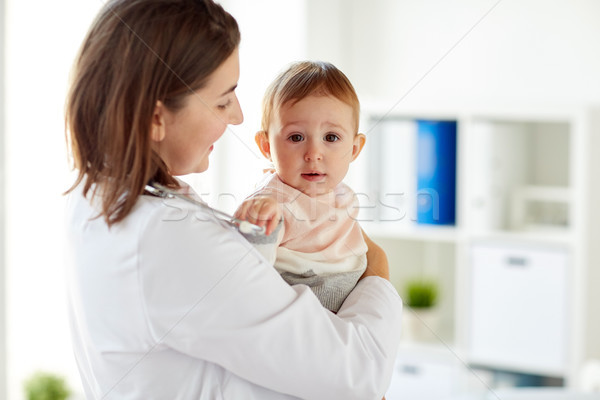 happy doctor or pediatrician with baby at clinic Stock photo © dolgachov