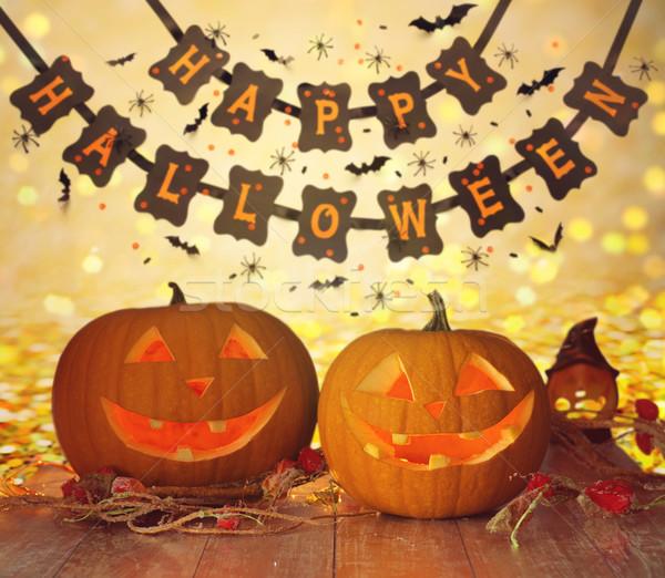 carved pumpkins and happy halloween garland Stock photo © dolgachov