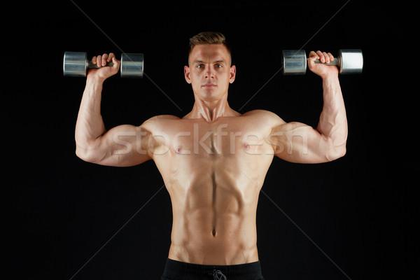 man bodybuilder with dumbbells exercising Stock photo © dolgachov