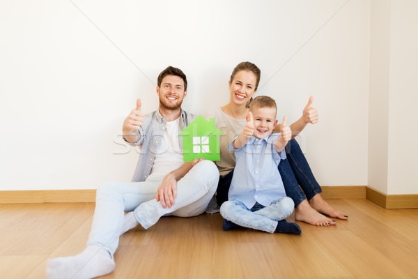 family with green house showing thumbs up at home Stock photo © dolgachov