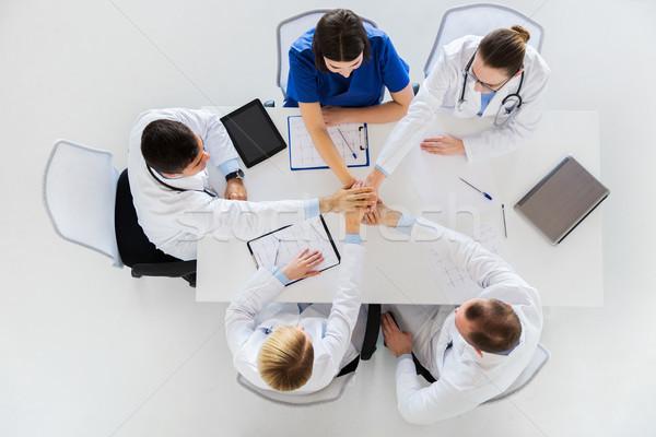 Csoport orvosok kéz a kézben együtt asztal gyógyszer Stock fotó © dolgachov
